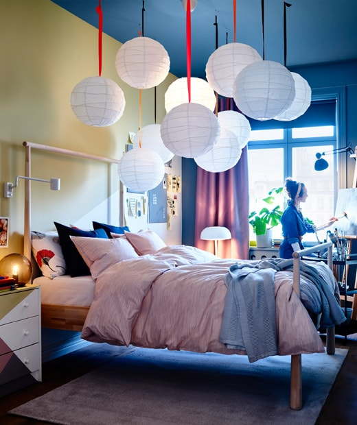 舖上粉紅色和藍色寢具的睡床,天花板掛有白色球形紙燈罩,一名女子在畫架前繪畫。