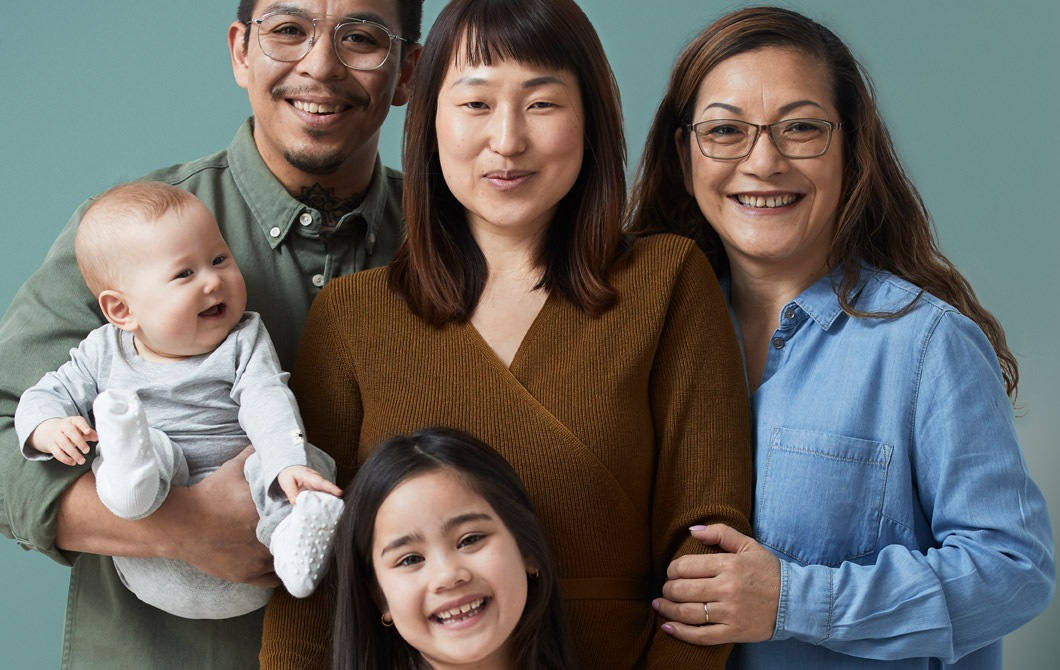 A family of five, all smiles from couple with a baby, a young daughter and a grandmother standing close together.