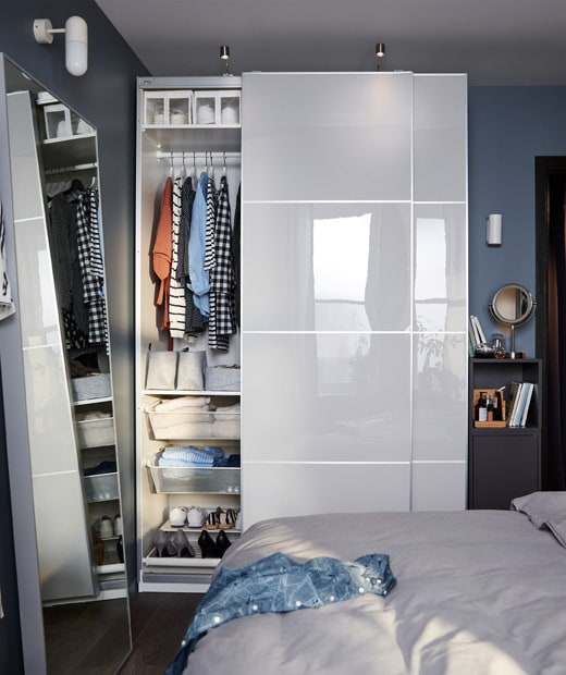 Small bedroom with wall section used in full by a PAX wardrobe, door aside revealing organised content, and a narrow cabinet.