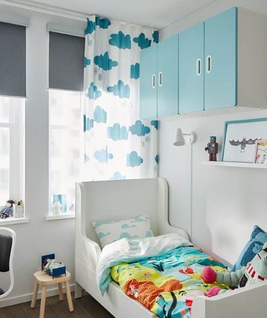 Small extendable bed in corner of a child's room. Colourful bedlinen and wall cabinets. Window with curtain and roller blind.