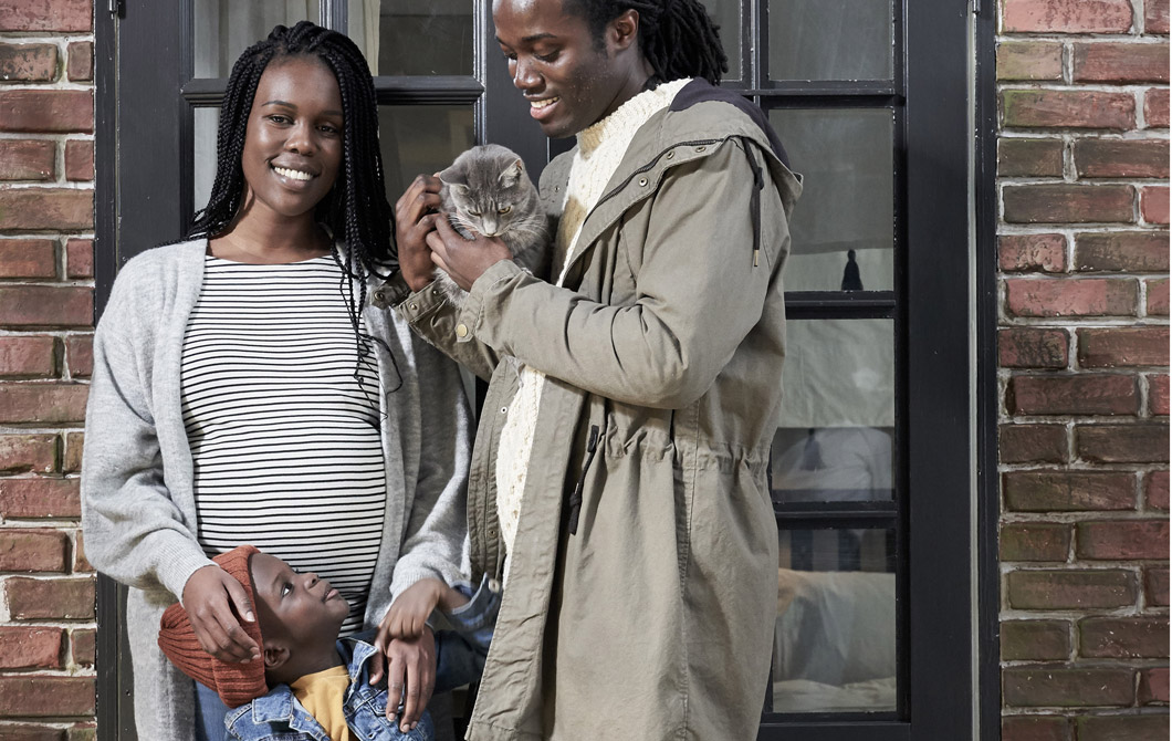 Smiling, late-twenties man and pregnant woman in front of a brick wall, a small boy in the middle; the man holds a cat.