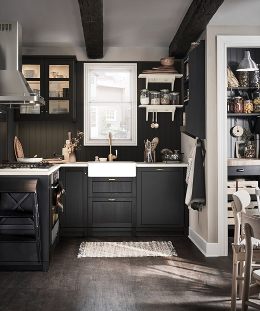 Neat, small, traditional-style kitchen with pantry and kitchen table; colour palette combination of dark and light surfaces.