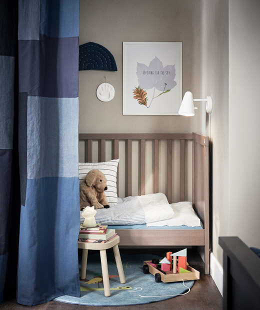 Corner of a room sectioned off with a curtain, behind it a child's cot with lamp, toys, books and a soft-toy puppy.