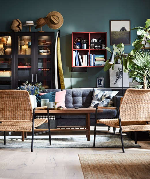 Living room with seating around a coffee table, a backdrop of a wall with a lot of open and display storage.