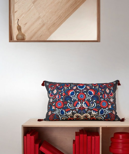 Wall section with mirror and a low bookcase standing alongside; a colourful, embroidered cushion placed atop.