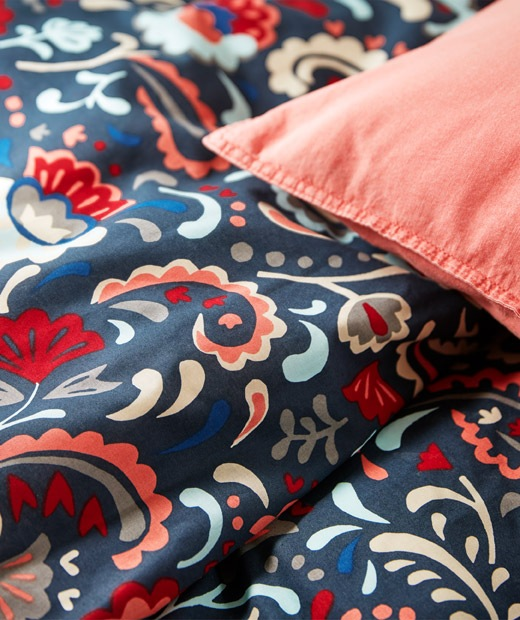 Section of a bed made with bed linen in bright colours and decorated with a traditional Swedish kurbits pattern.