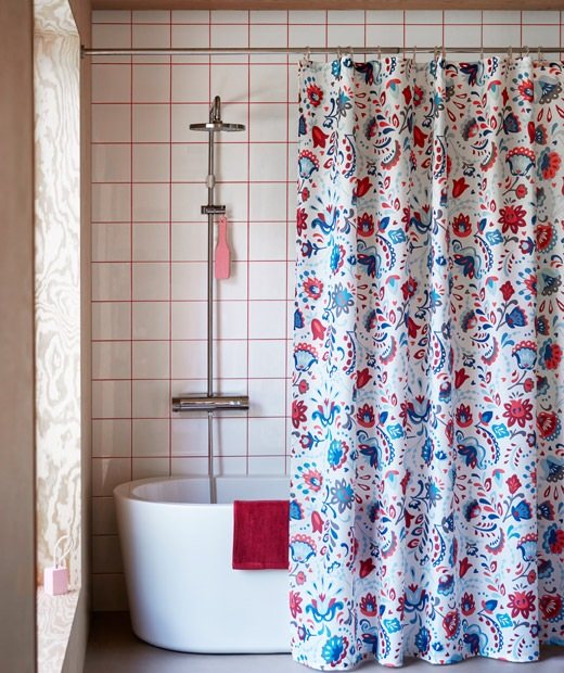 Bathroom interior with a richly patterned shower curtain hanging in front of a bath with full-length shower.