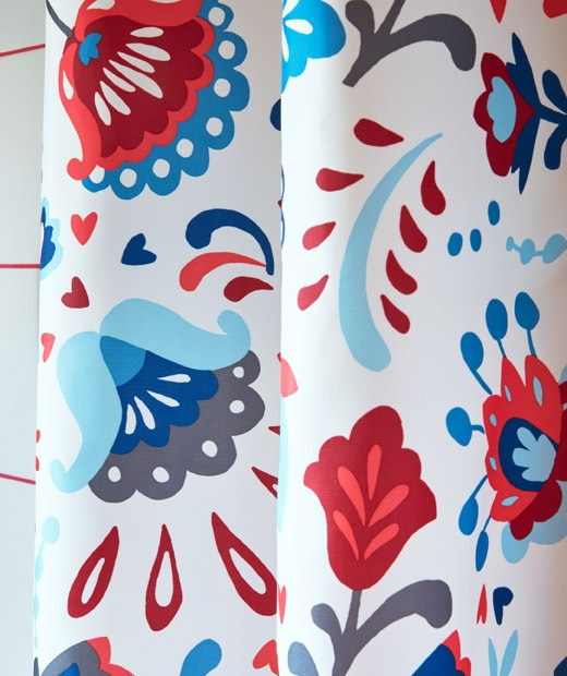 Zoomed-in section of a shower curtain, brightly coloured and decorated with a traditional Swedish kurbits pattern.