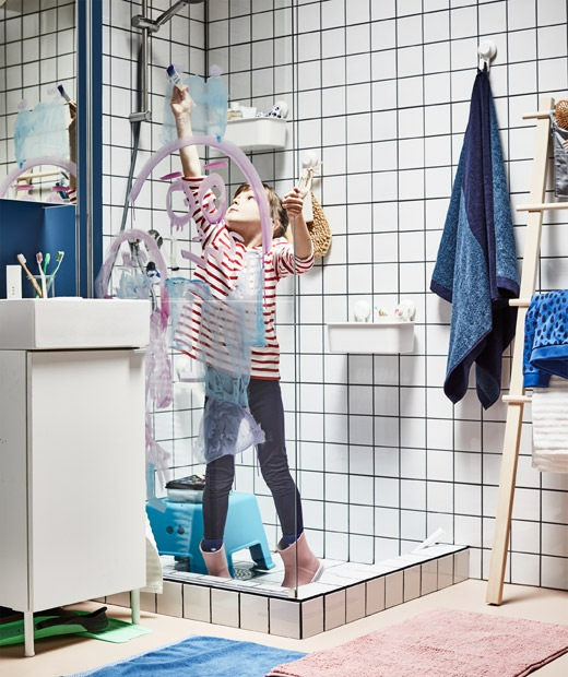 Fully clothed child, including rubber boots, standing in a dry shower, painting with watercolours on the glass partition.