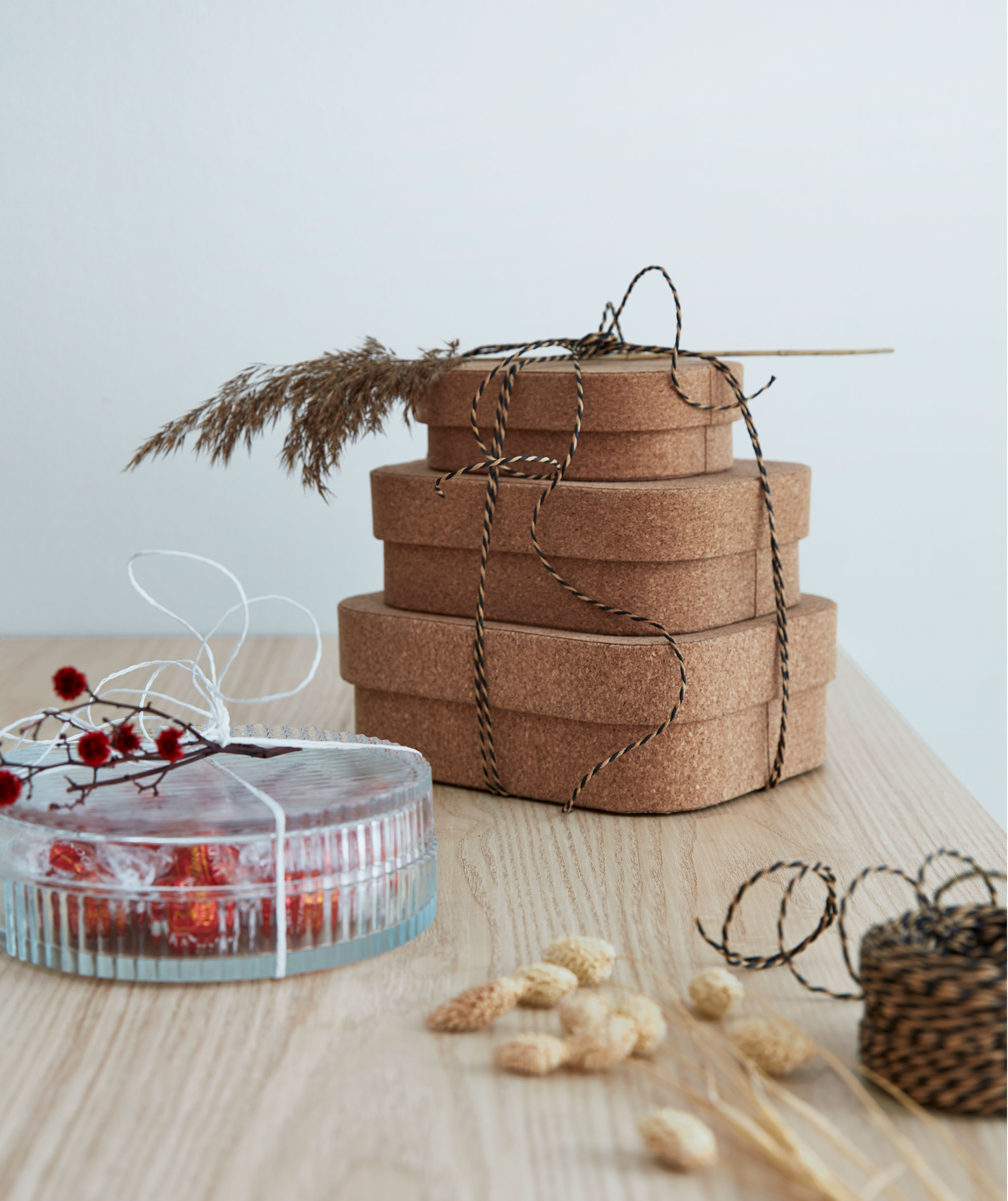 Three cork boxes tied together with string, decorated with grass stems; a gift-wrapped glass jar of candies next to it.