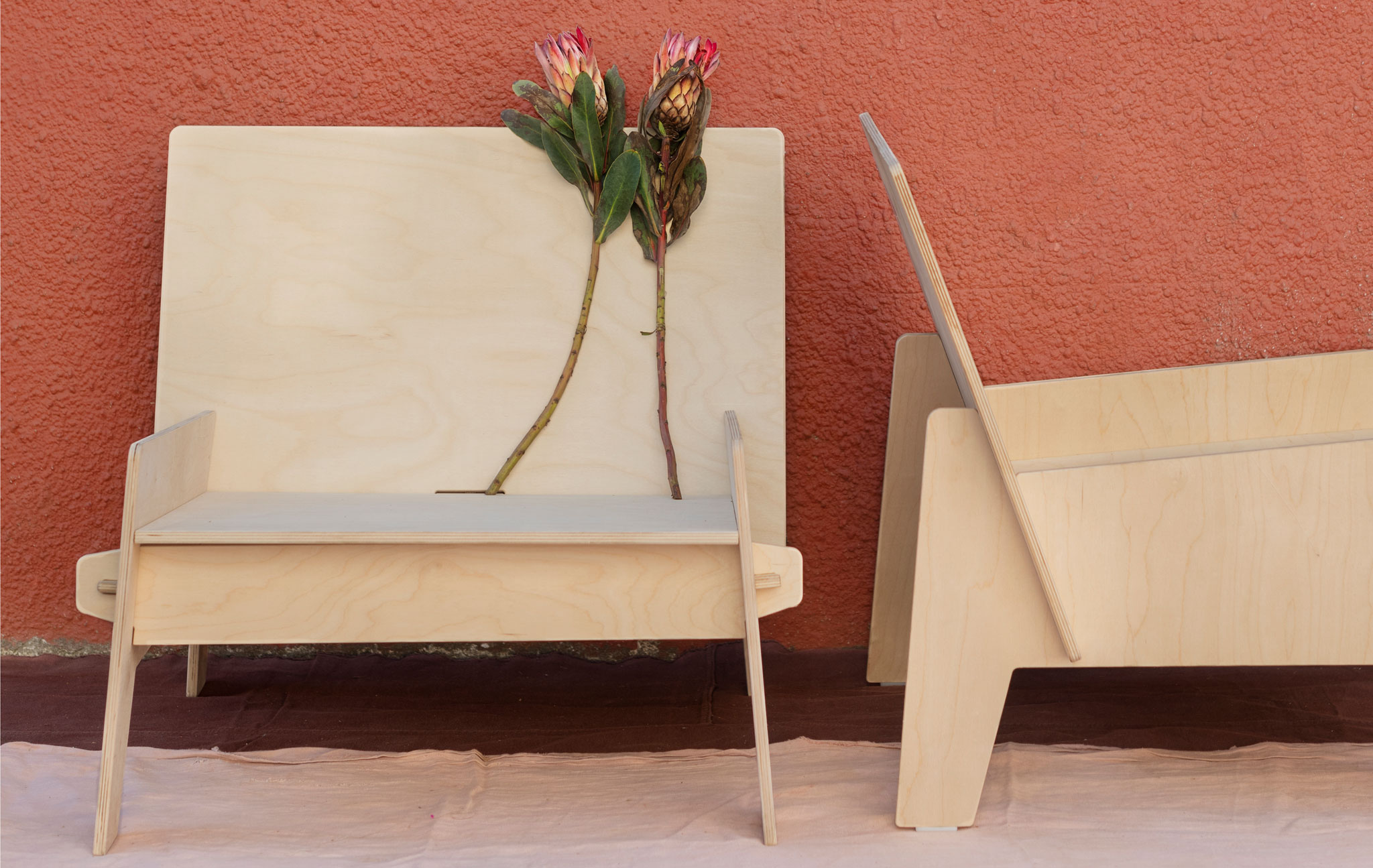 Two low, wide chairs, placed perpendicular from each other, wholly made from fitted, flat sheets of plywood.