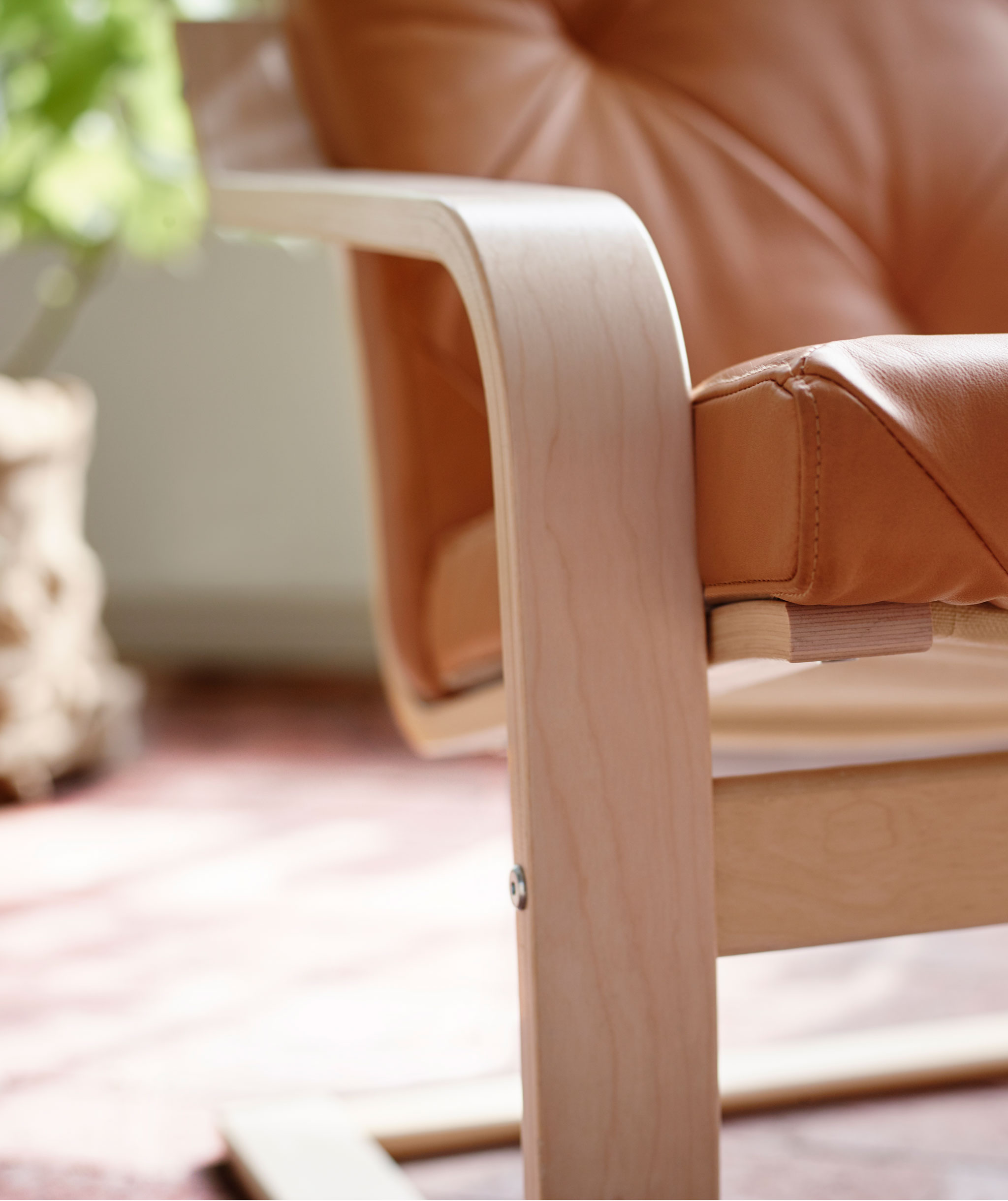 A plywood armrest and adjacent frame and seat details of an armchair, placed in a sunlit room; plant in the background.