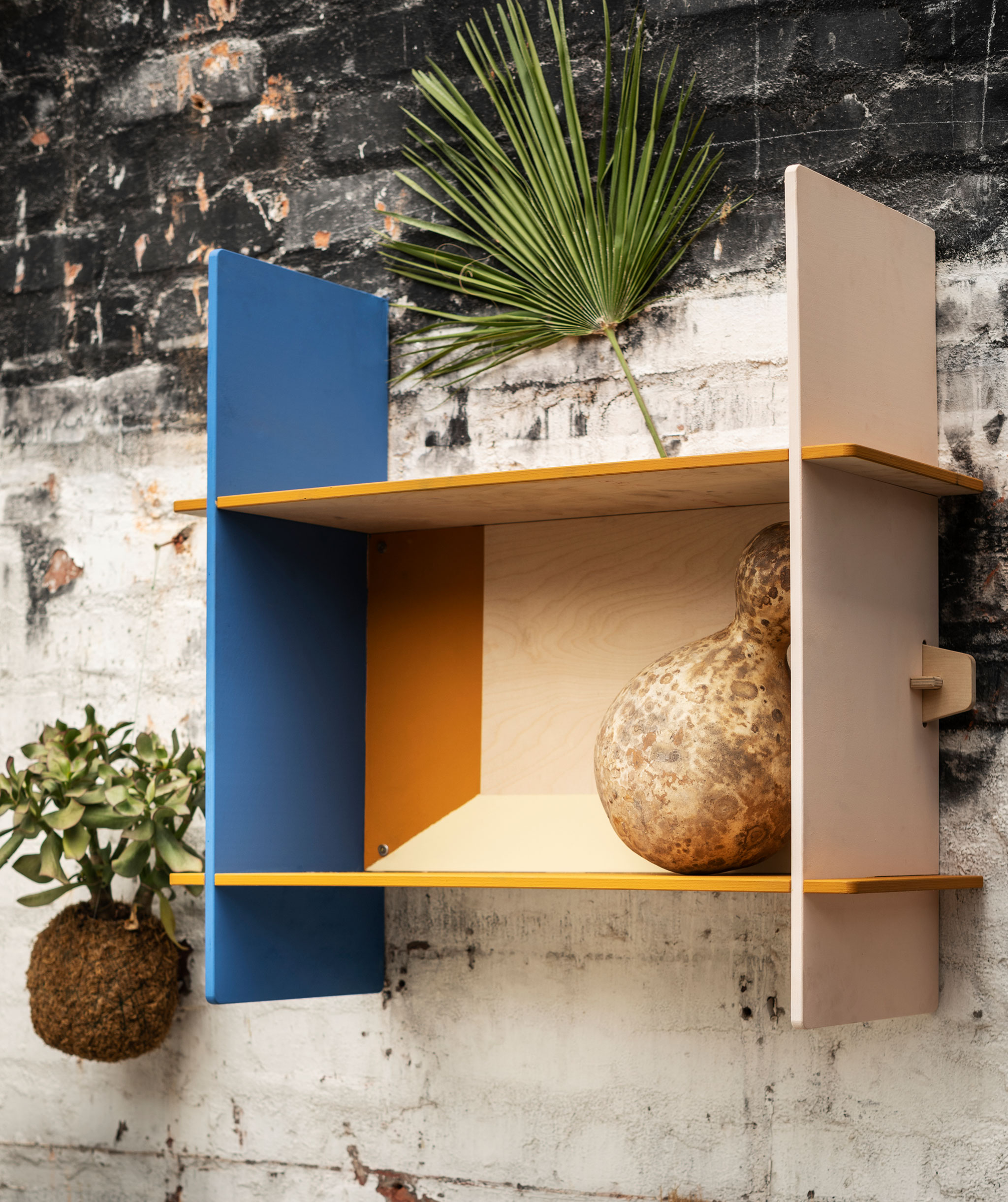 Small, rectangular wall shelf made of plywood, mounted on a rough brick wall (presumably outdoors).