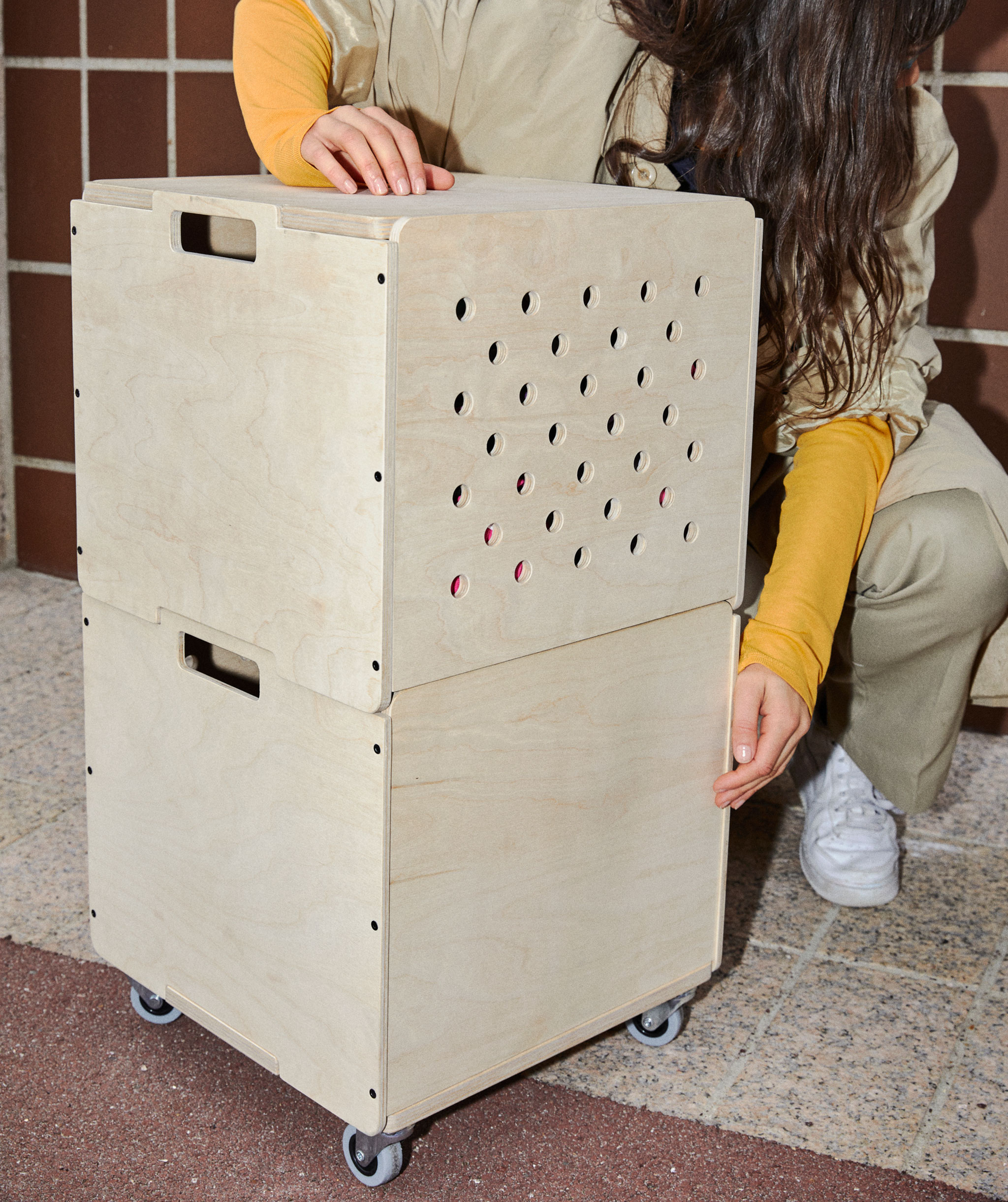 Two cube-shaped storage boxes made out of plywood, stacked on top of each other. The lower box has castors.