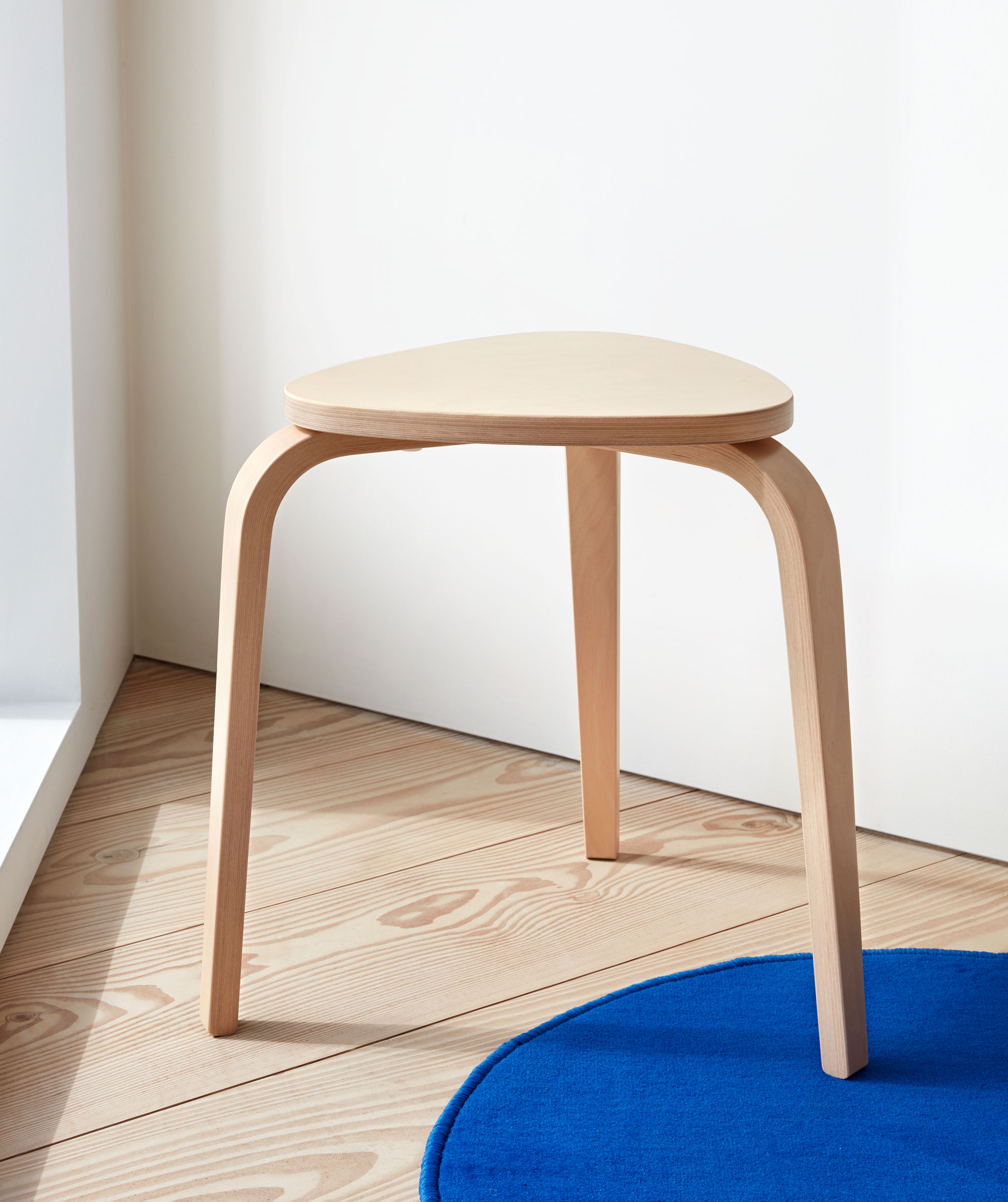 Three-legged, light-wood stool standing in a sharp-angle corner on a wooden floor, one leg on a small blue rug.