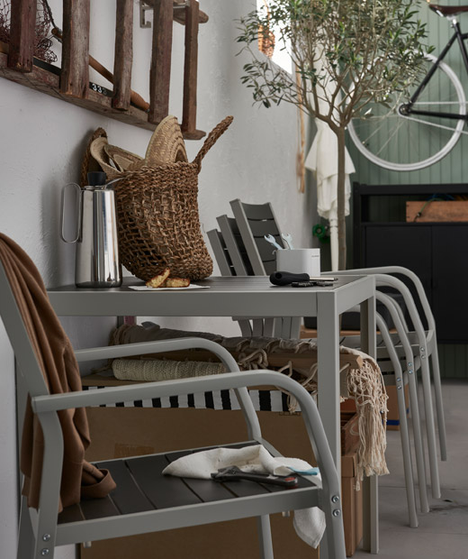 Garage-like interior with stacked outdoor furniture and other summery items; a single chair placed beside the table.