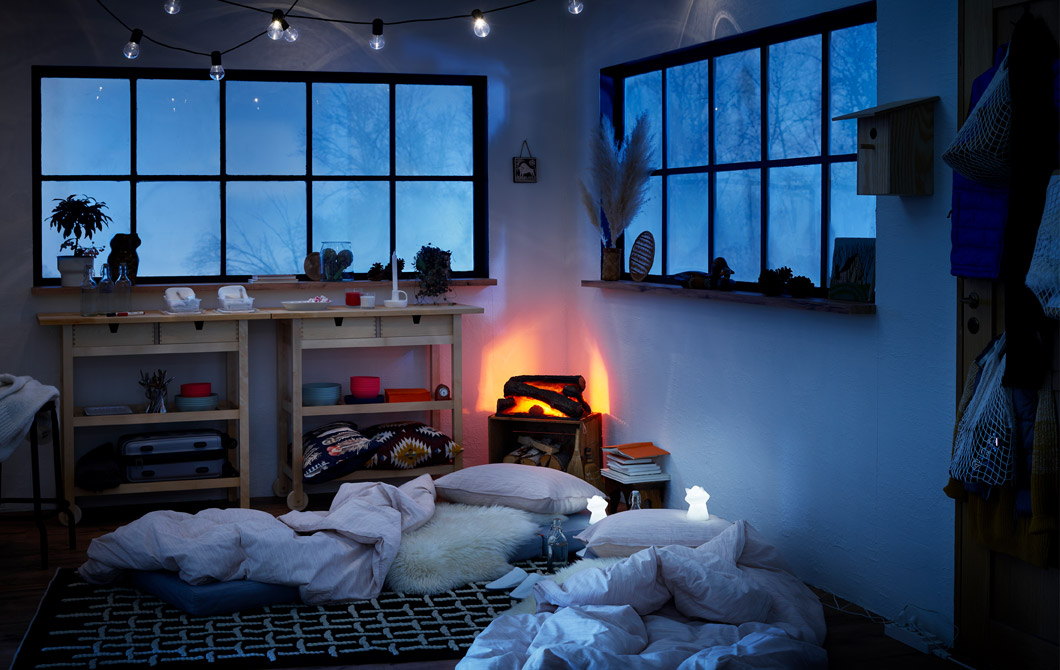 Wintery log-cabin style interior, mattresses on the floor made as temporary beds, LED night lights beside them.