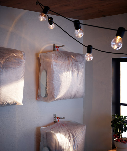 Arranged and hung on a wall, storage cases hold identical bedding and night-time accessories (as if prepared for guests).