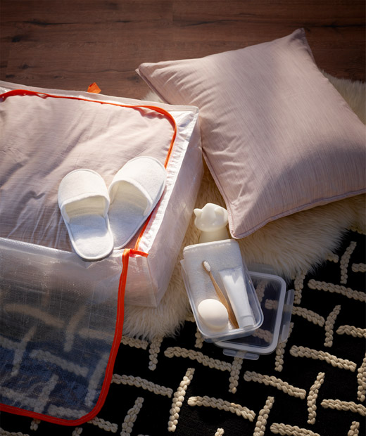 Laid on the floor, a half-unpacked storage case holds bedding, slippers, toothbrush and -paste, soap, towel and night light.