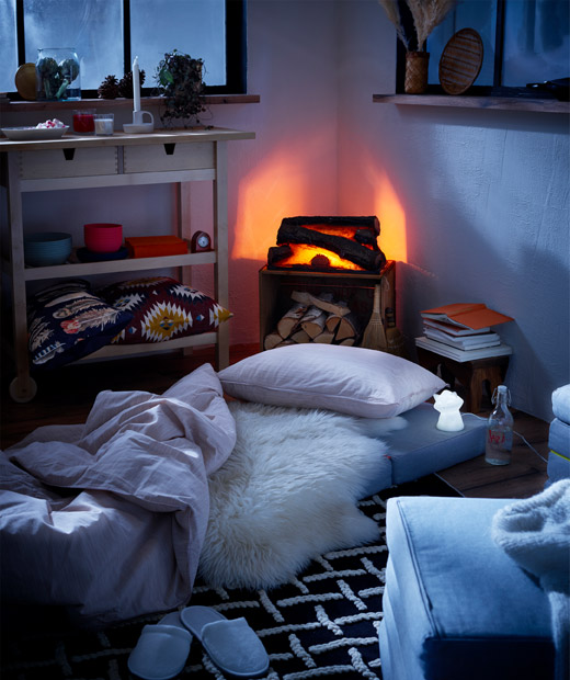 Log-cabin style interior with fake fireplace and mattresses on the floor as temporary beds, LED night lights beside.