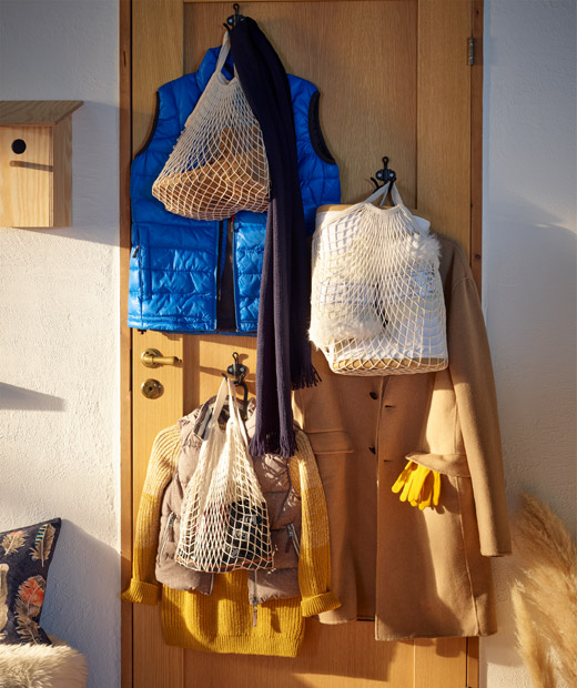 Wooden door with hooks showing signs of arrived guests: coats on hangers, net bags filled with personal belongings.