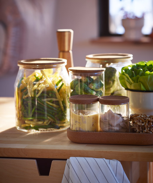 Assortment of small or side dishes – vegetables, herring and more – in different-size glass jars, placed on wooden surface.