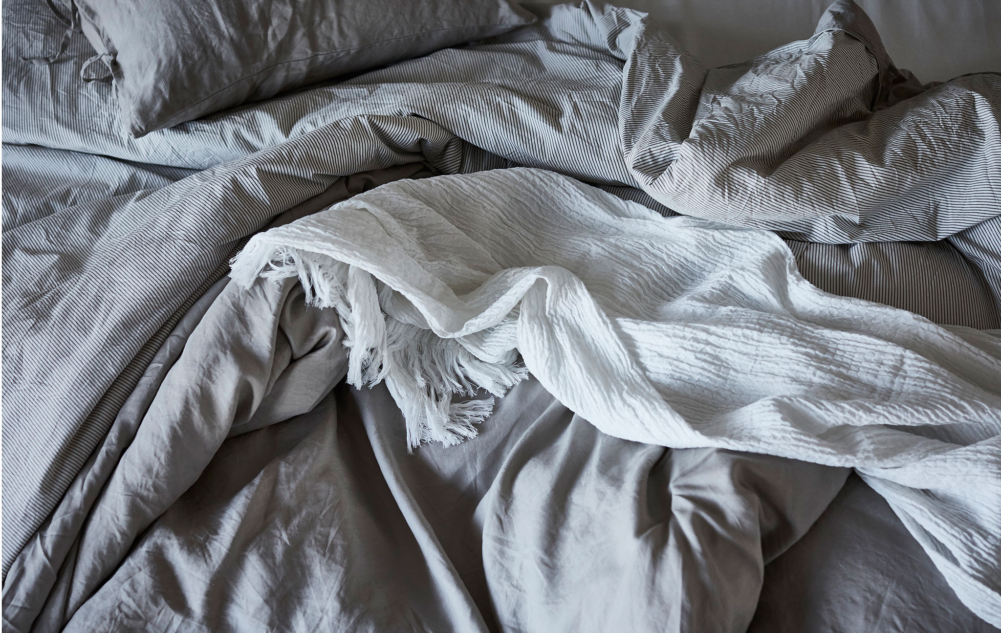 Section of an empty, slept-in bed with creased, fluffy, one-colour bedlinen; a throw untidily lying on top.