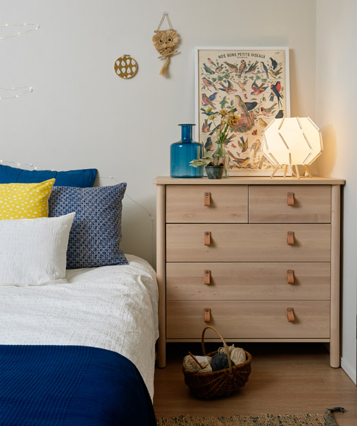 The corner of a bed with blue and white bedding next to a chest of drawers in a white bedroom.