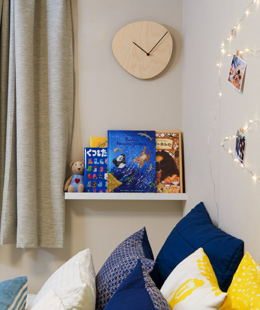 A simple wooden wall-mounted clock and a bookshelf filled with children's books above a cushion-filled bed.