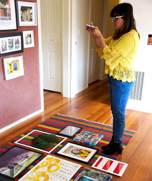 Abeer taking a photo of framed pictures laid out on a rug.
