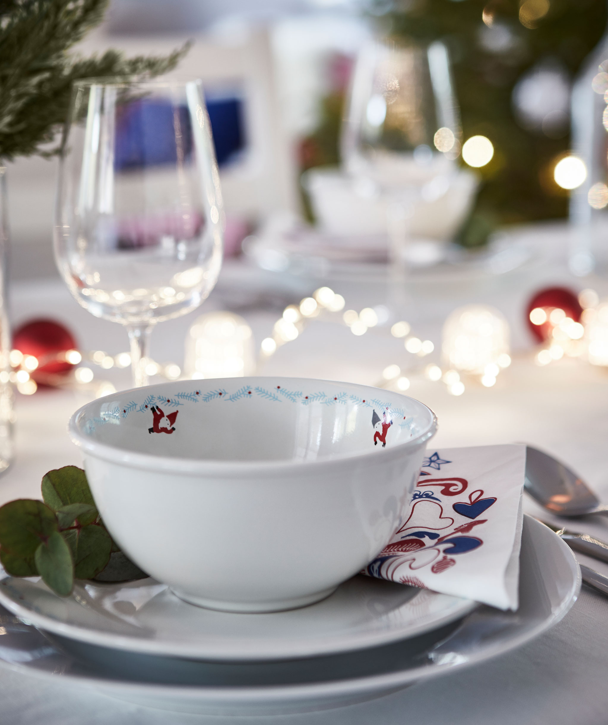 One-person section of festively set table. Multiple plates, lighting chains on table, winter-green decorations, wine glass.