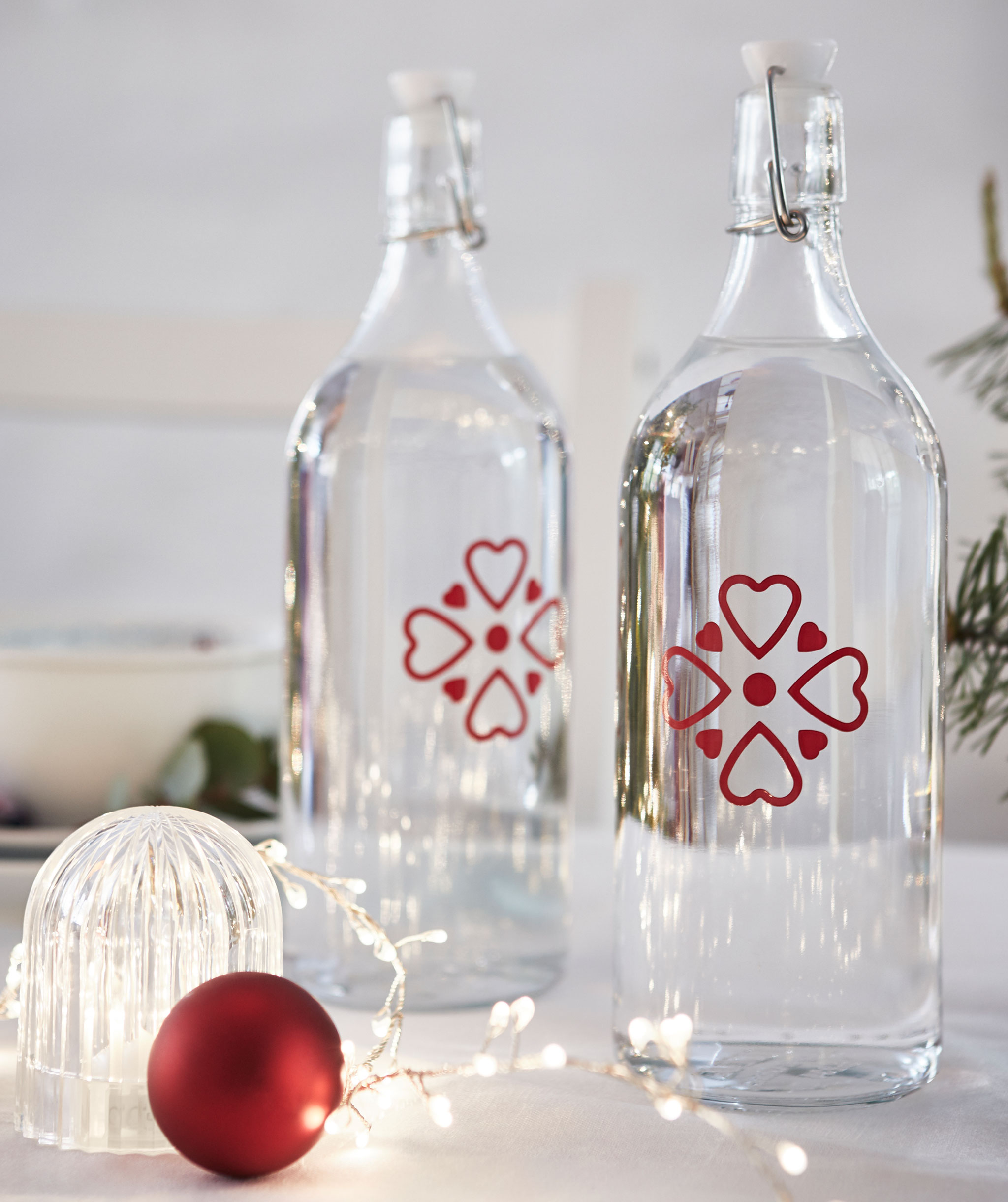 Two glass bottles, clear with small red decorations, standing on a table next to a decorative LED light and lighting chain.