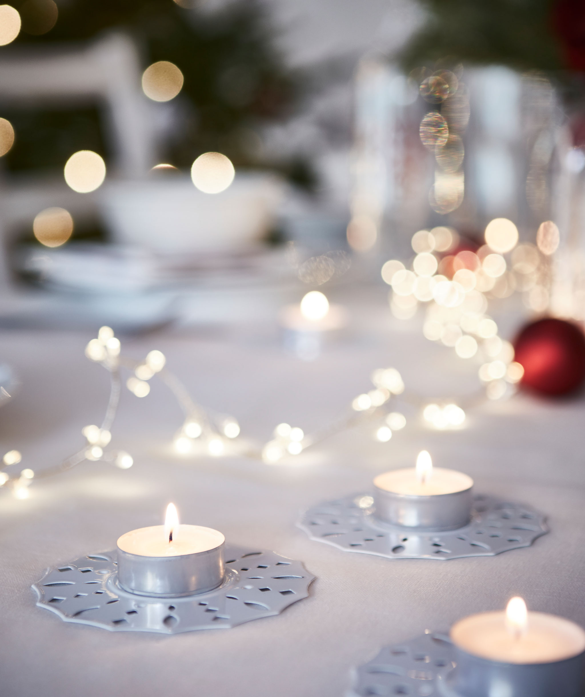 Tea lights in decorative holders placed on table; out-of-focus background of a big table set for Christmas dinner.