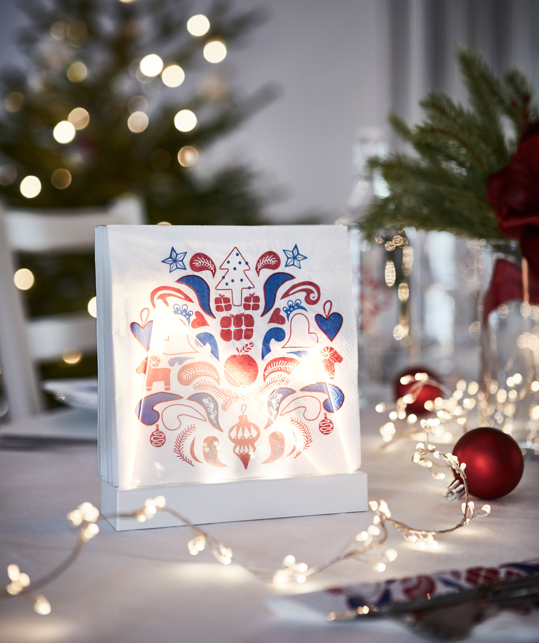 Festively patterned paper napkins standing upright in a lit stand, thus adding to the holiday-set table it's placed on.
