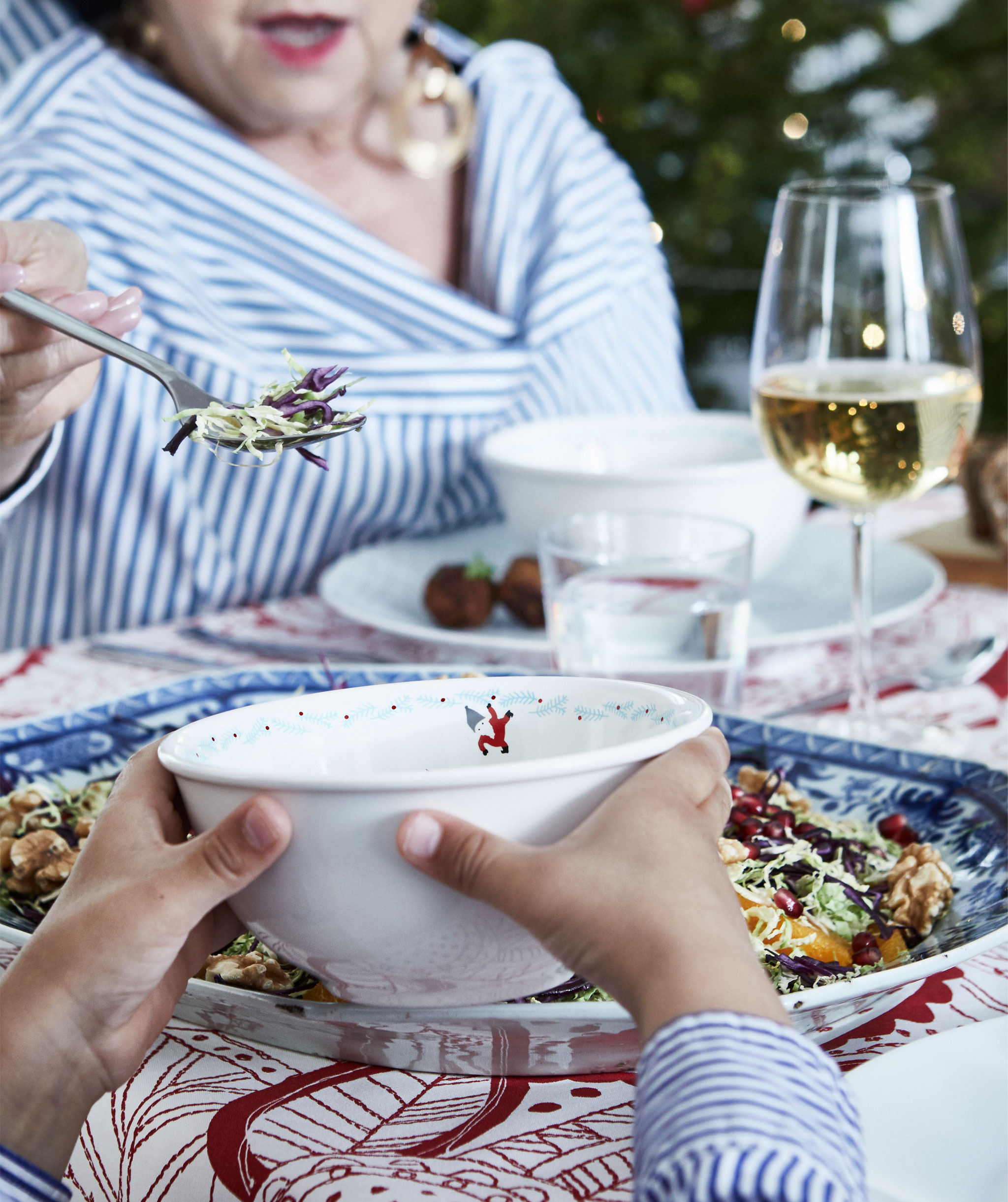 Section of holiday-set table, including filled plates and glasses. An older person serves food into a bowl held by a child.