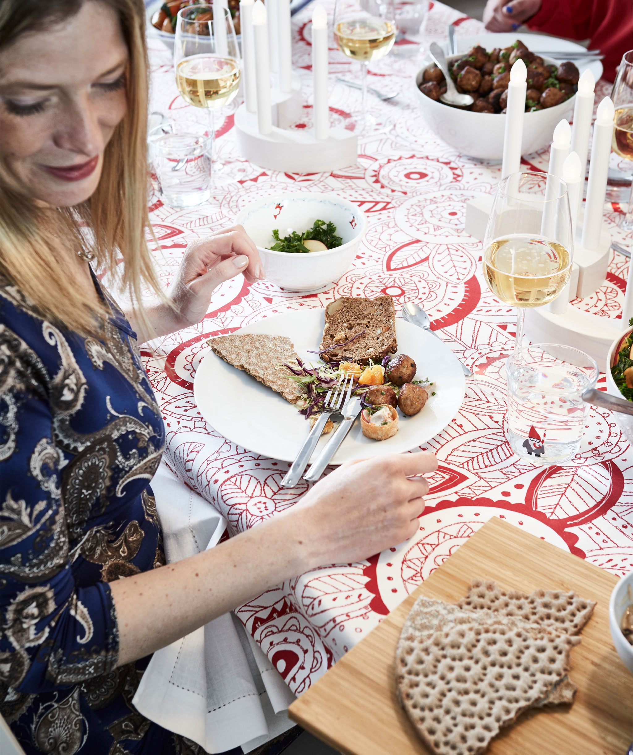 Section of decorated, festively set table with food, drinks and people. A woman is proffered a tray with crispbread.