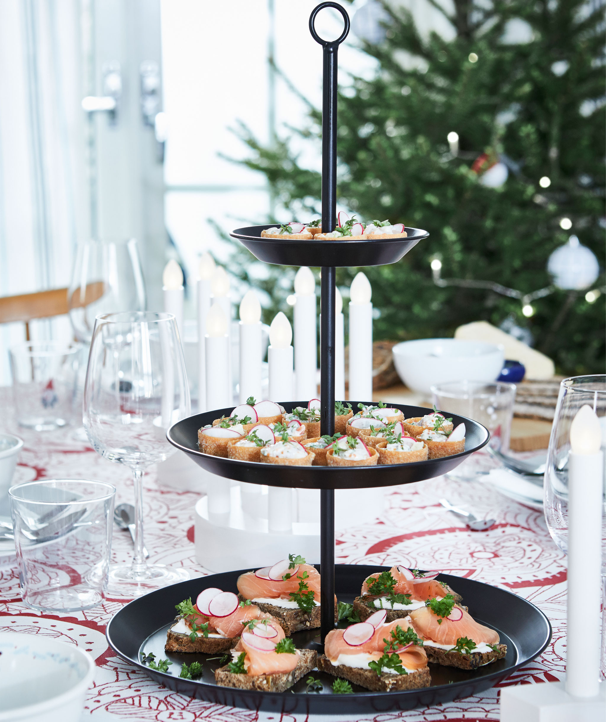 Serving stand filled with elaborate hors d'oeuvres, standing on a table set for a feast. Christmas tree in the background.
