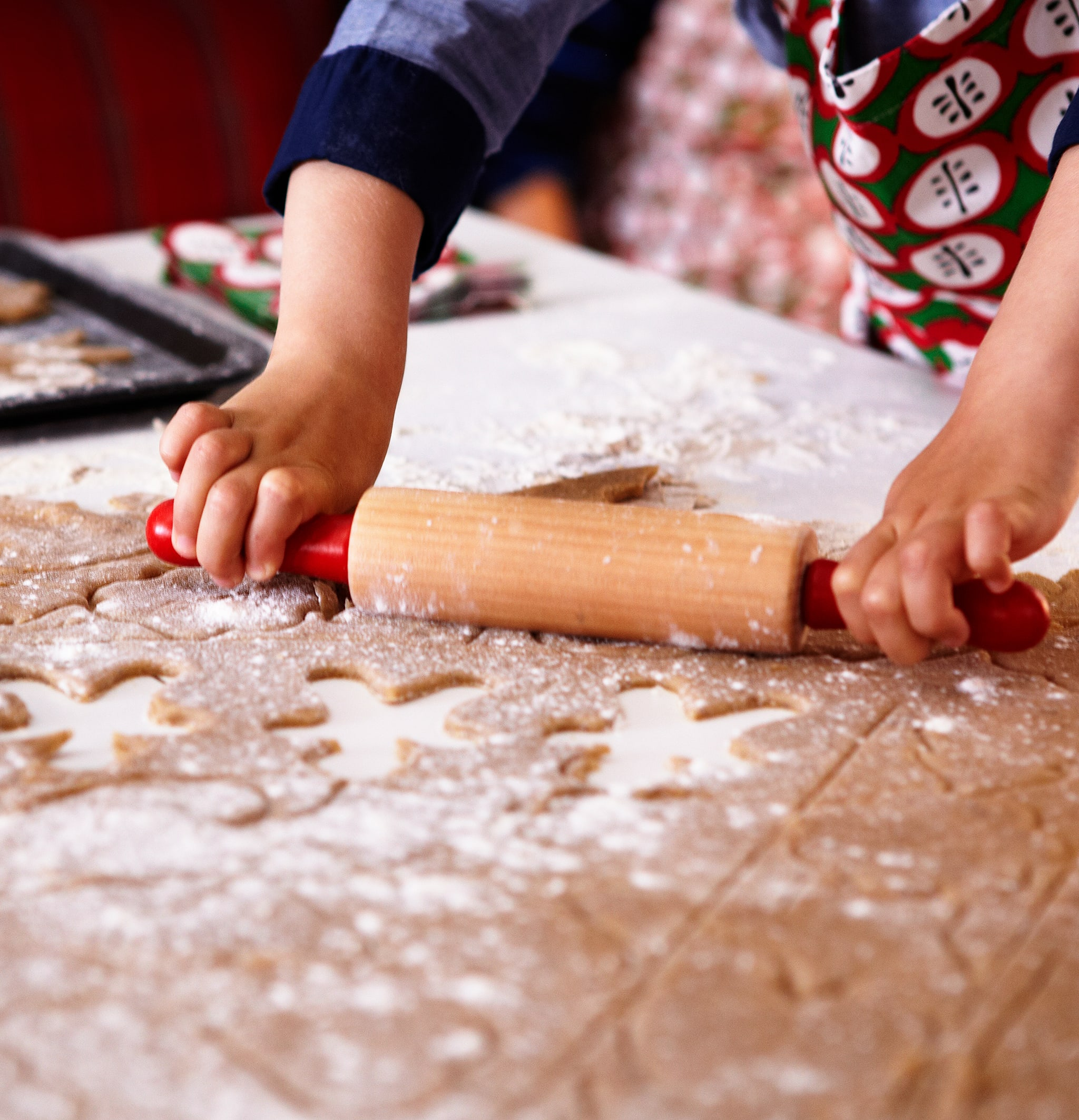 The hands of an apron-clad child hold a rolling pin, working a sheet of flour-dusted gingerbread dough with shapes cut out.