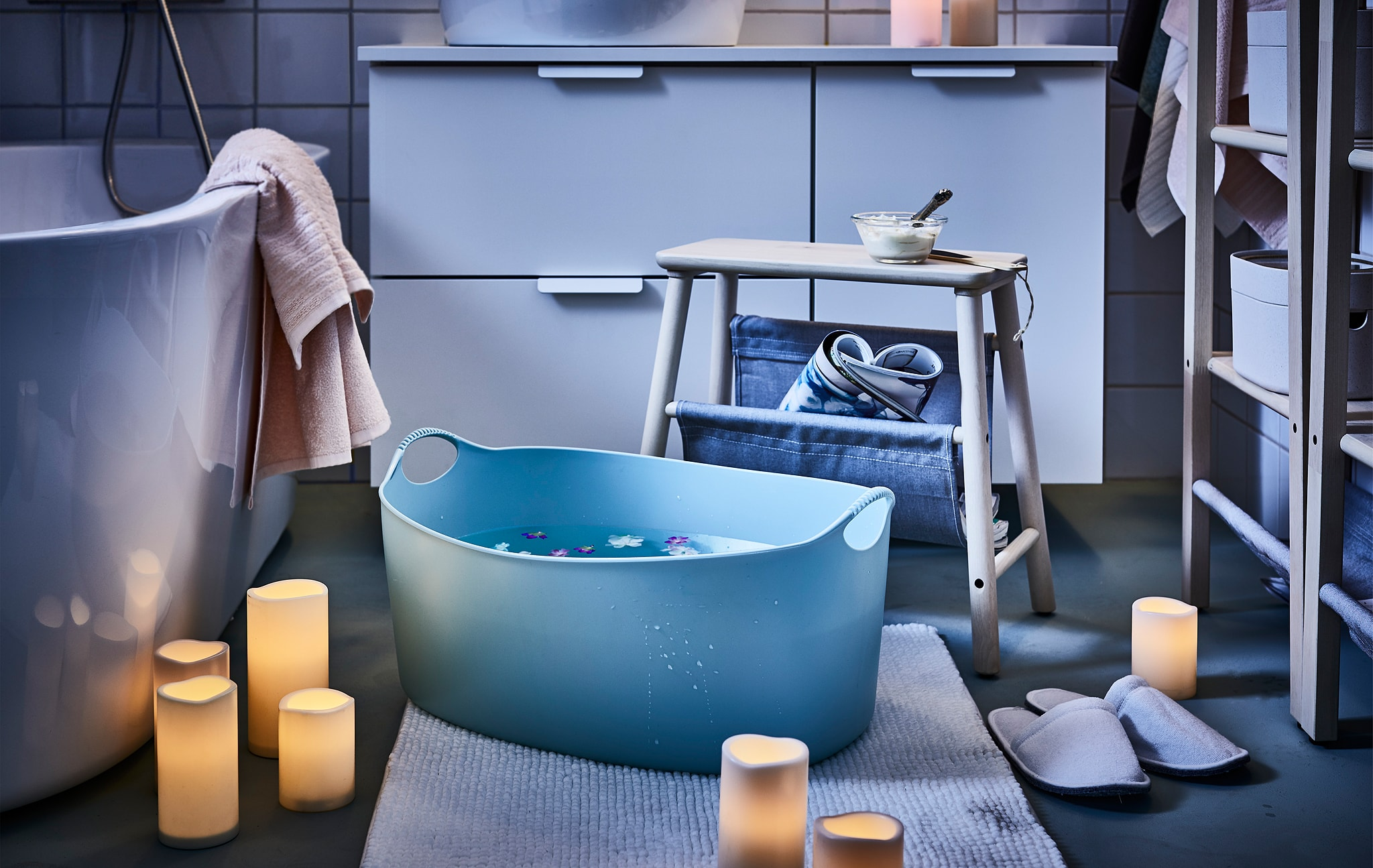 Bathroom mood-lit by scattered LED block candles; a stool placed next to a big footbath, flowers floating in it.