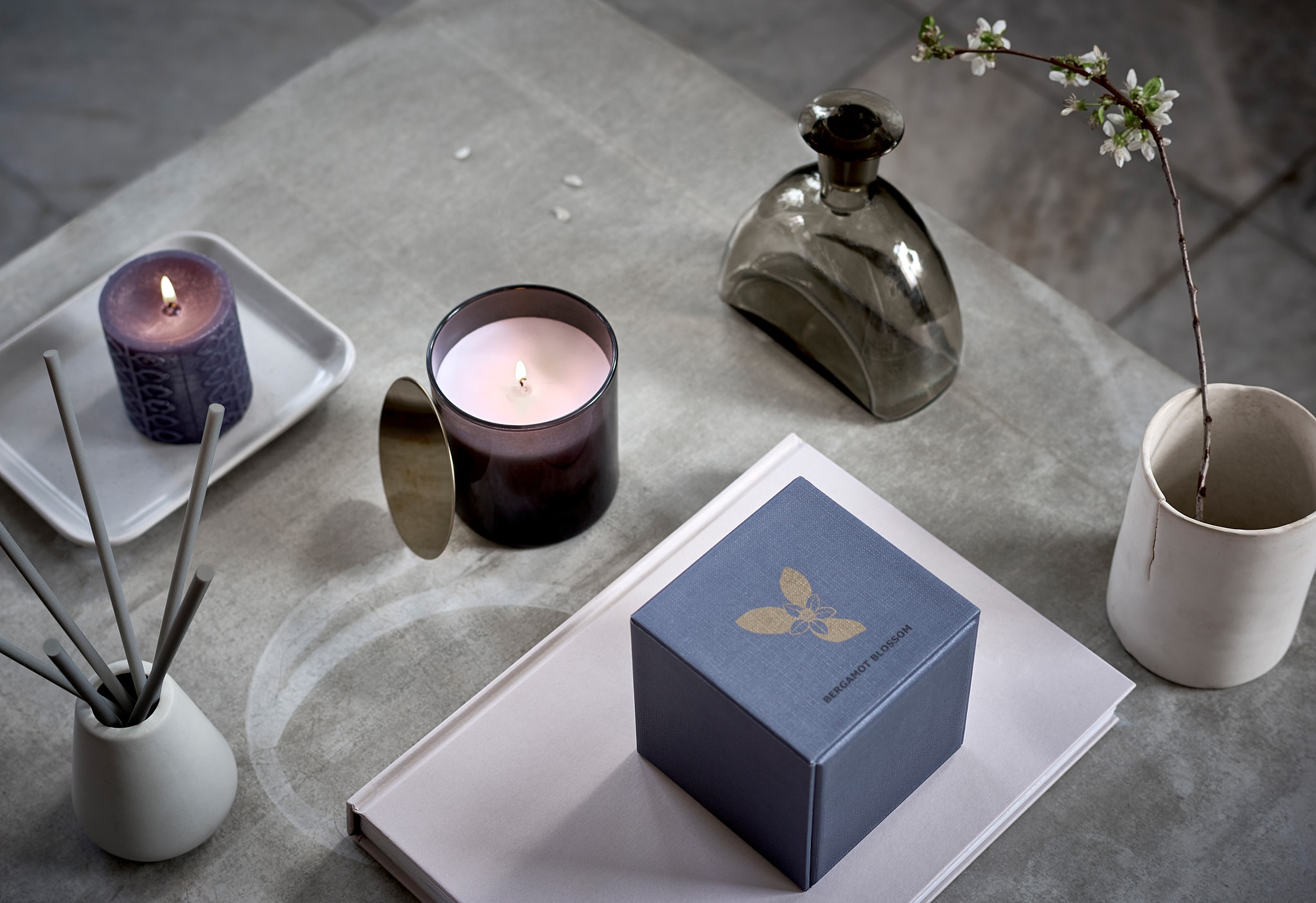 Surface with symmetric arrangement of scented candles, a cup with a twig in bloom and similar spa-style decorations.