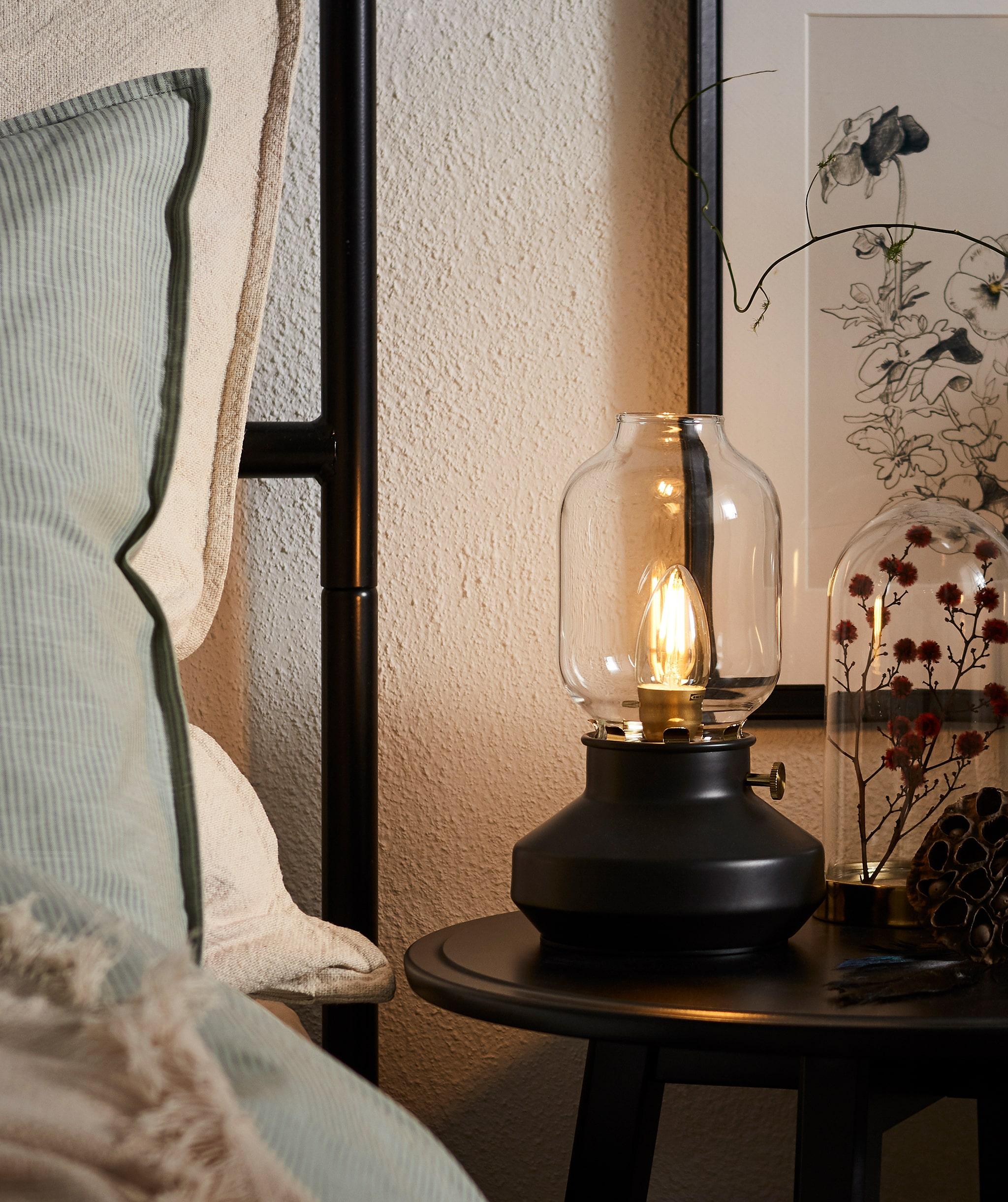 採用高床頭板的床邊,枕頭豎起,圓形床頭几上放著類似煤油燈的LED燈。