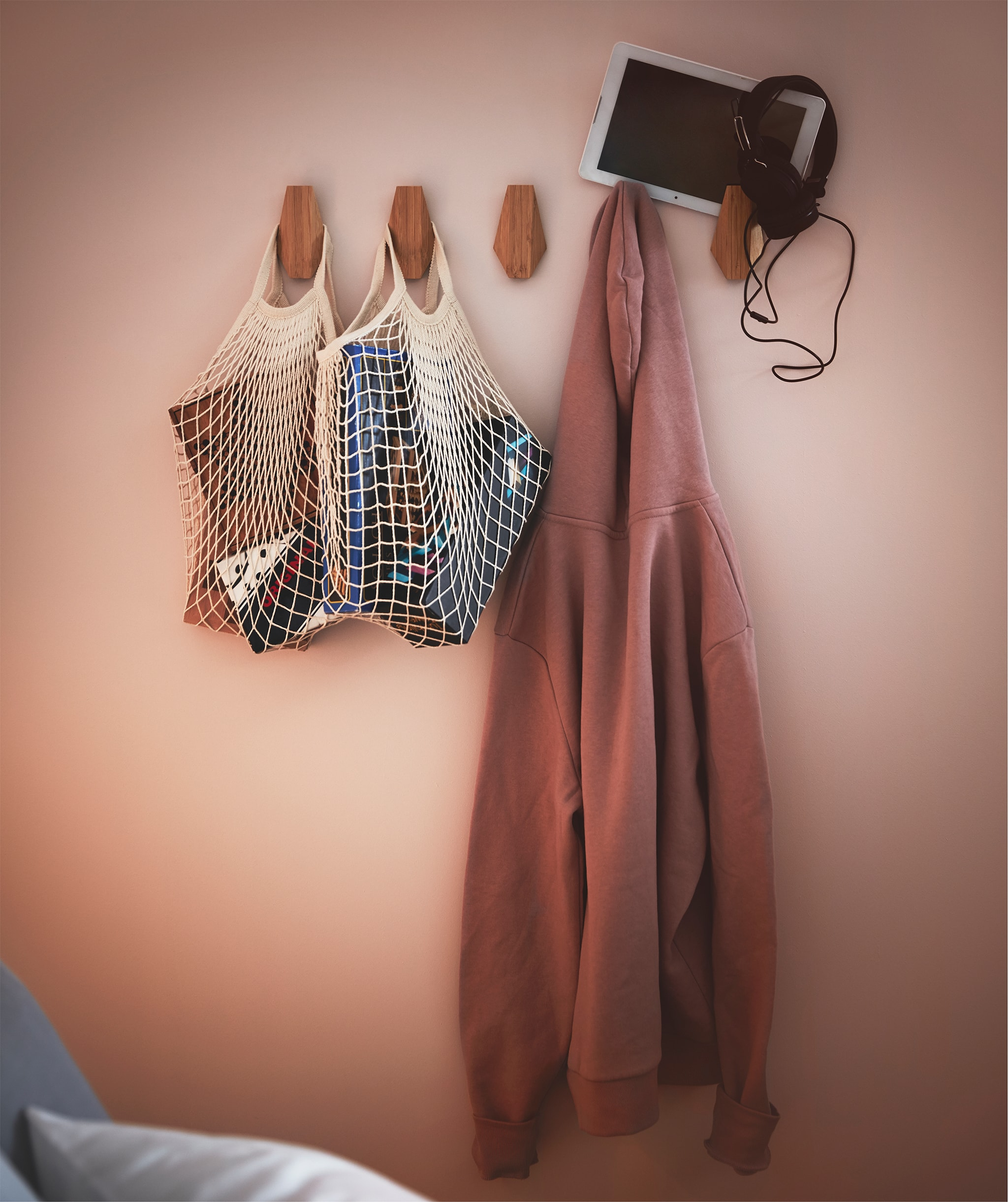 Section of bedroom wall fitted with row of SKUGGIS bamboo hooks holding filled net bags, a hoodie and a tablet with earphones.