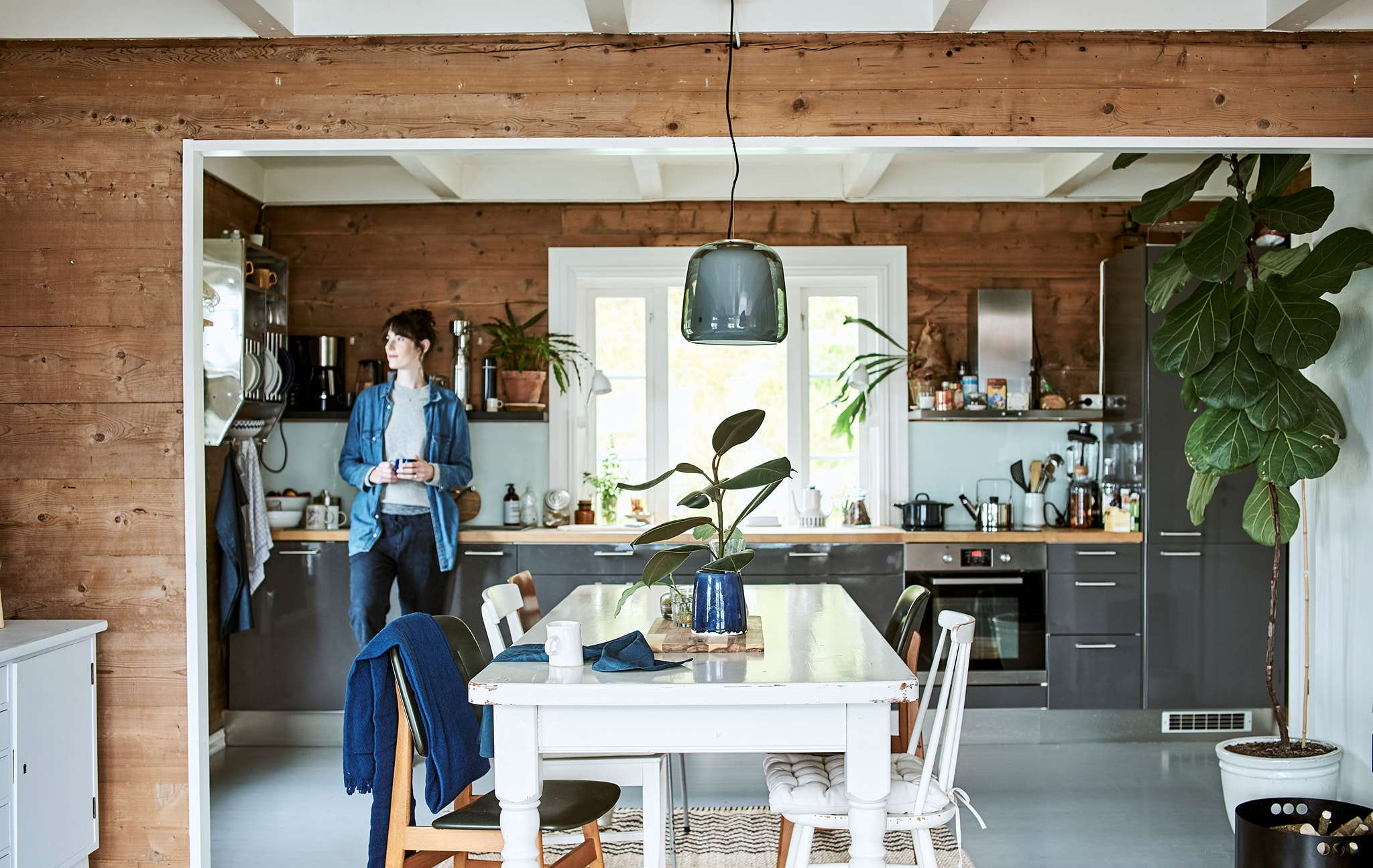 A woman leans on a shiny grey cabinet in a galley kitchen that opens to a dining room with white wood table and chairs.