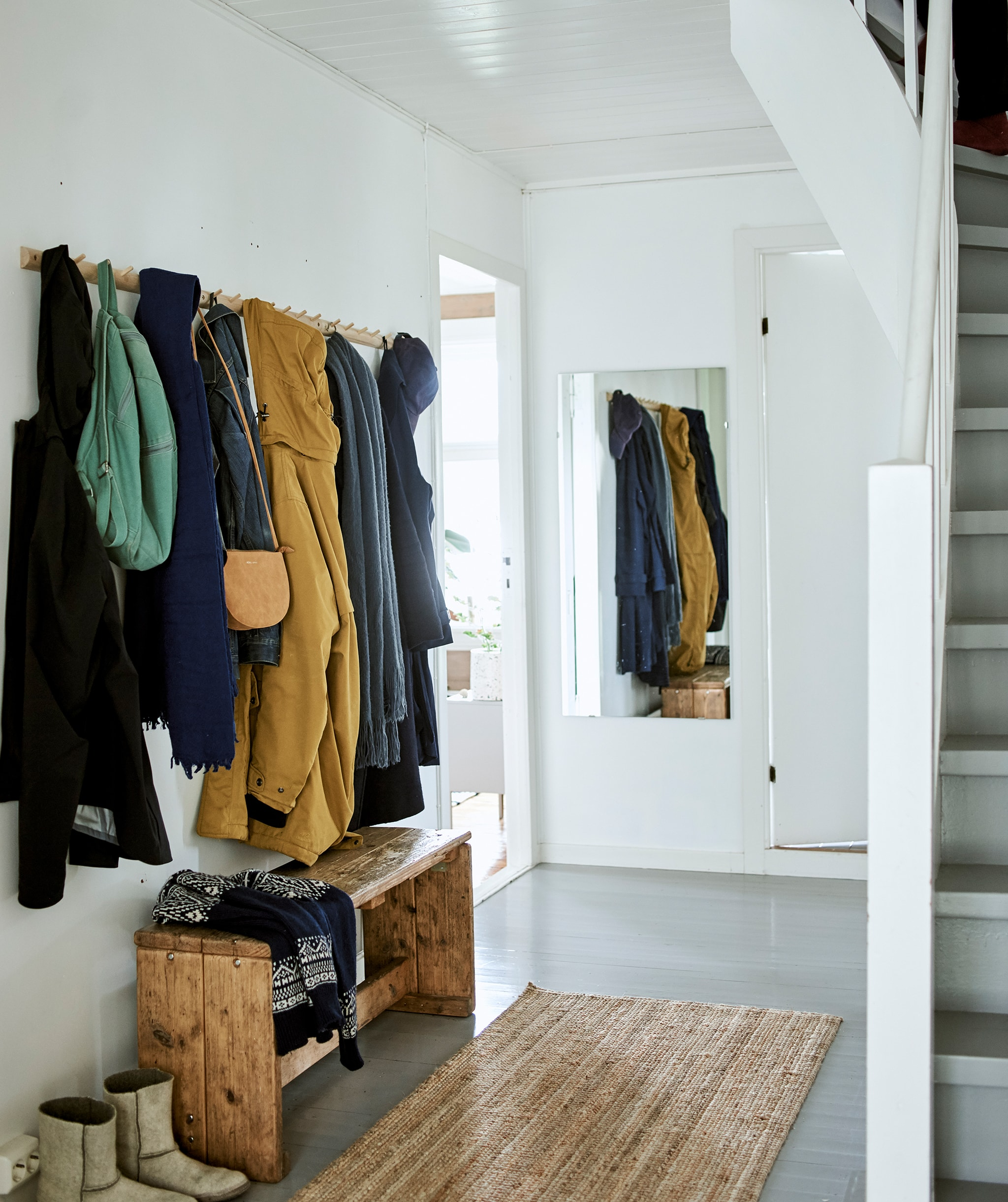 A white hallway with a row of Shaker-style hooks for coats, wooden bench, sisal floor runner and wall-mounted mirror.