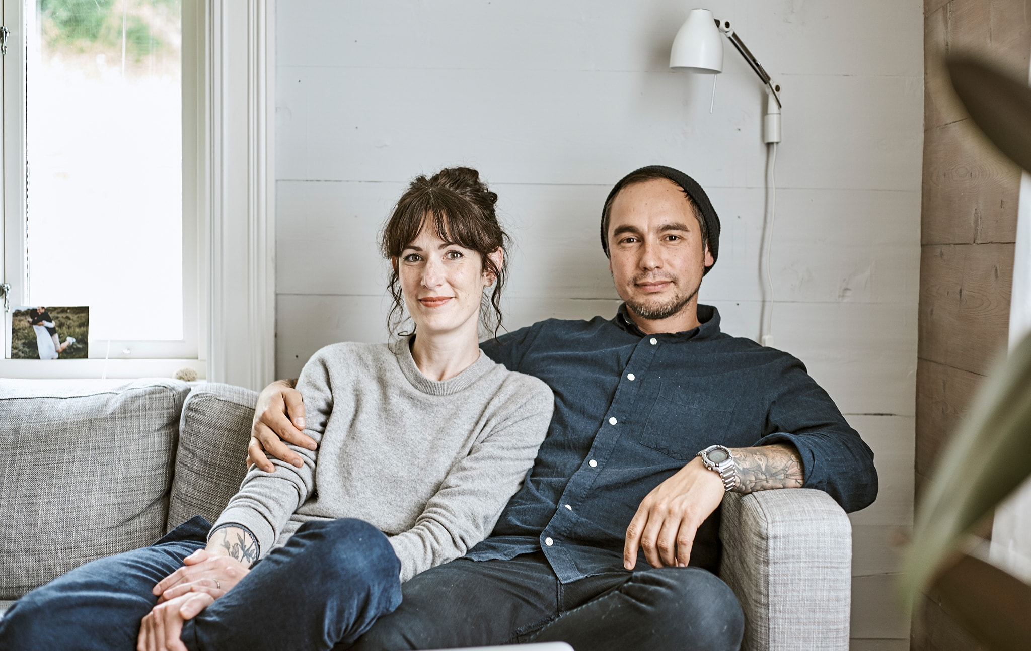 Rena and Sam sitting on the sofa together in their Norwegian farmhouse.