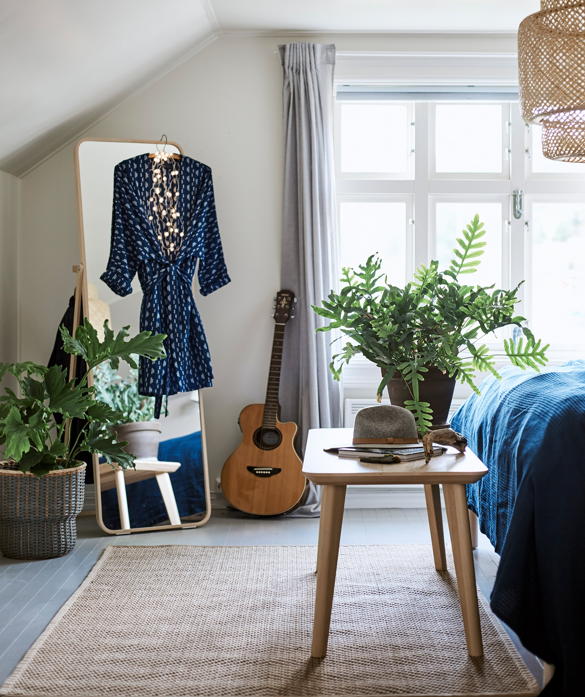 A bedroom with a woven ceiling lamp and rug, freestanding mirror with dress hanging on it and a bench at the end of the bed.