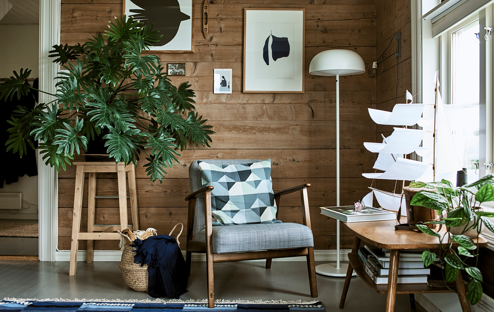 A rustic living room with a wood-framed armchair, white floor lamp and stool used as a plant stand for a big leafy plant.