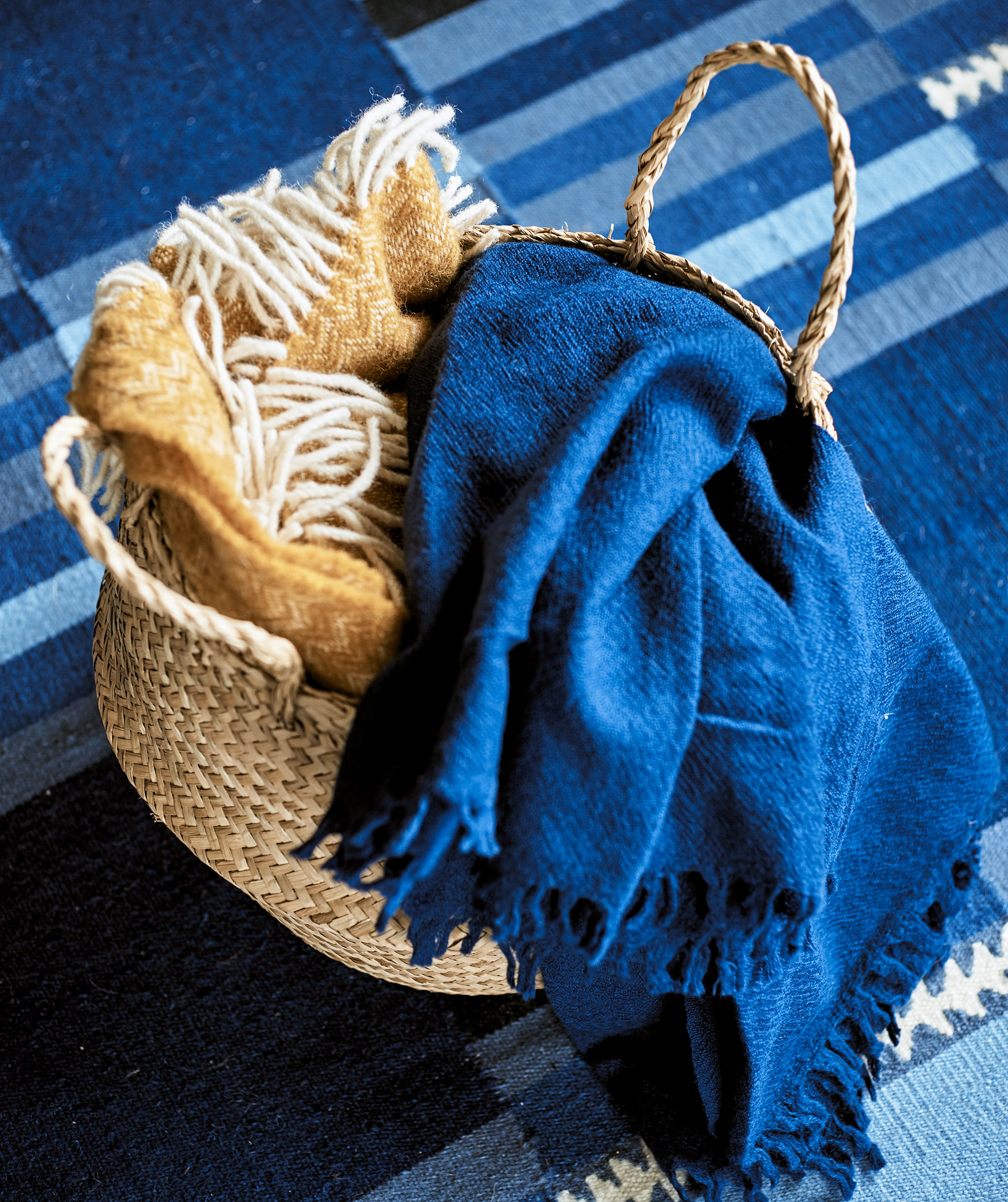 A woven basket containing a yellow fringed throw and a blue linen throw on a blue stripy patterned rug.