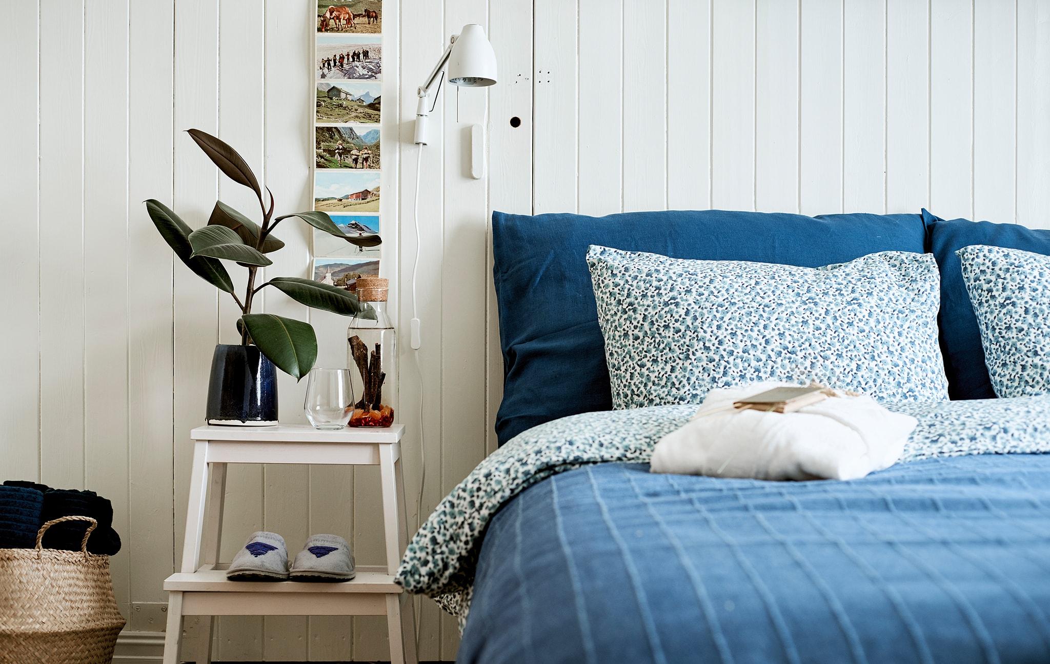 採用藍色寢具的整齊床舖,兼作角几的腳踏上有一瓶維他命水和水杯。