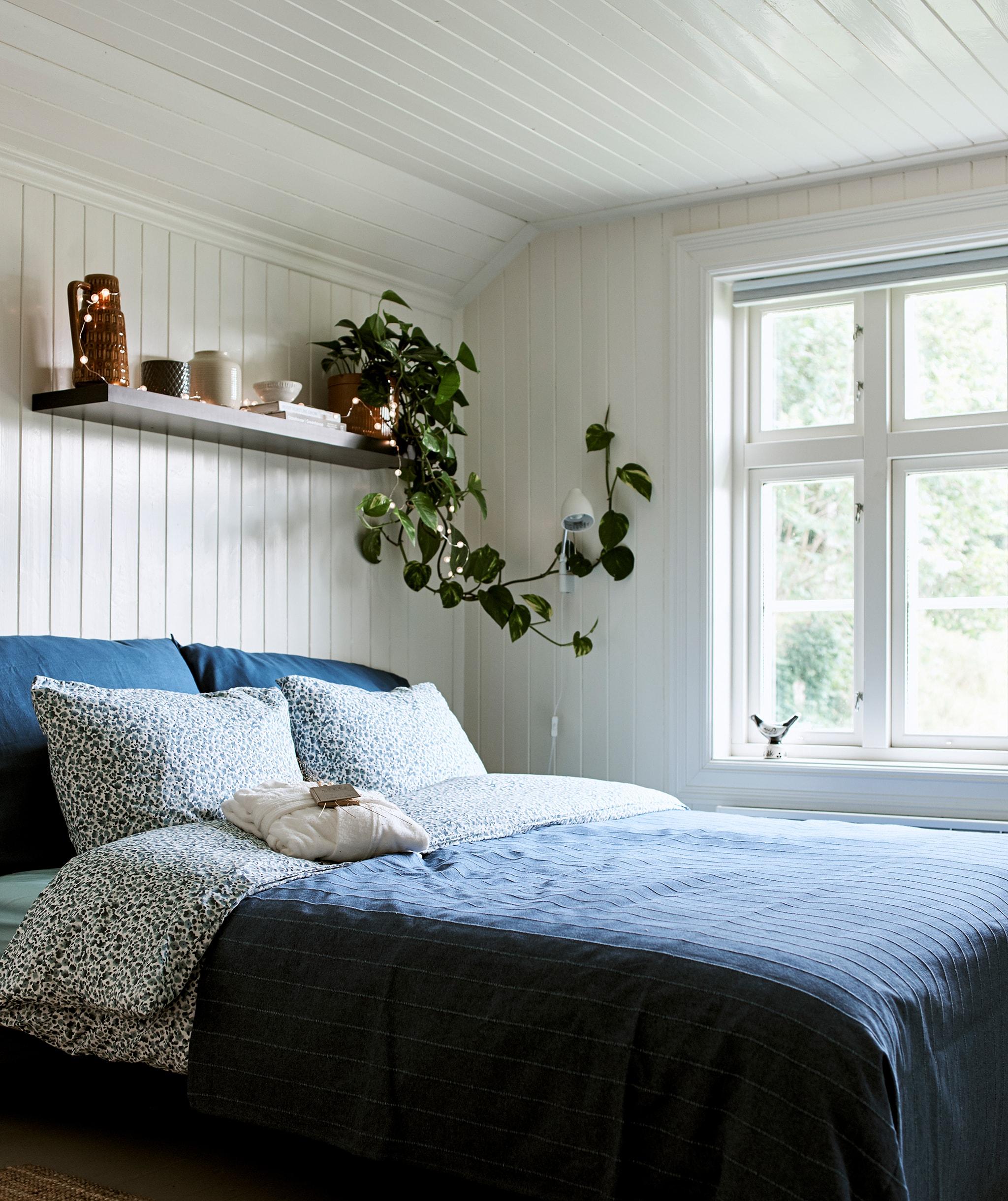 舖上白色木牆板的農舍睡房,睡床舖上藍色寢具,上方的牆架用作貯物和展示擺設。